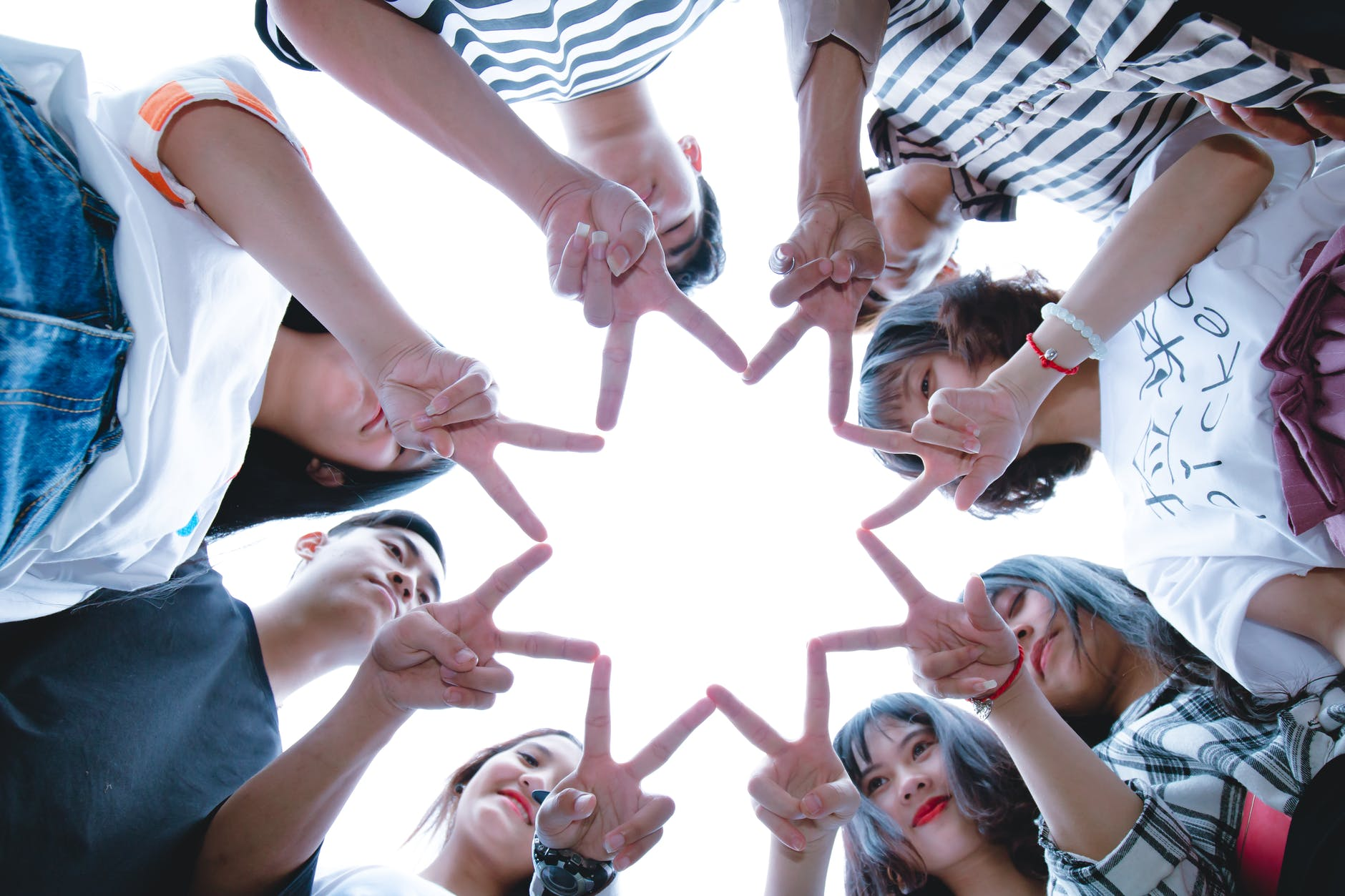People in a circle creating a star symbol with their fingers.